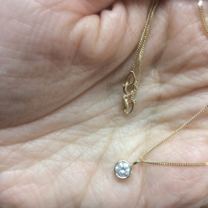 palm of Jenny's hand holding necklaces